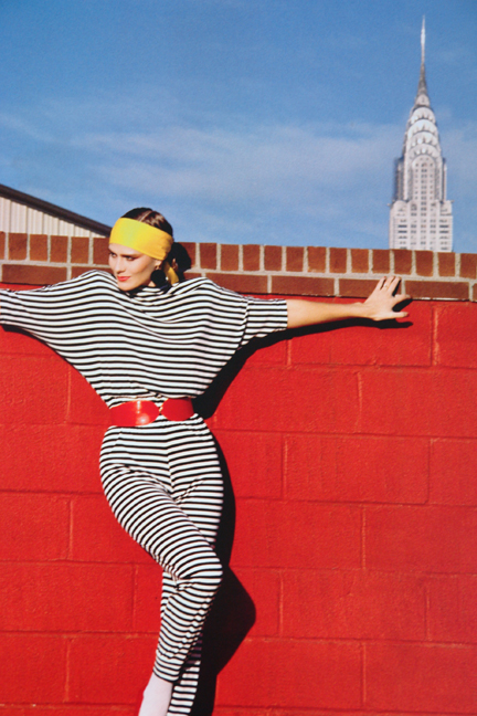 "page from the book, ""70s Style & Design"" showing a model wearing a black & white striped jumpsuit posing in front of a red brick wall with the Chrysler Building in the background"