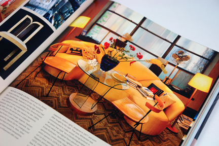 "page from the book, ""70s Style & Design"" showing a siting room with a large yellow sofa"