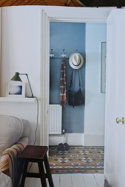 view through a whitewashed doorway into a hallway with encaustic tiled floor and shabby chic coat rack
