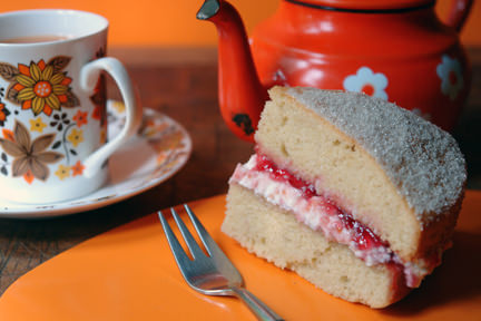 Slice of sponge cake with raspberry and mascarpone cream with a cup of tea