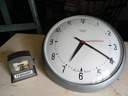 vintage industrial desktop perpetual calendar and vintage dome-faced Smiths wall clock