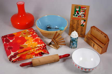 group of vintage items soon to be added to the H is for Home website including a medium sized orange & white Cathrineholm Lotus enamel bowl, wooden rolling pin with red handles, pottery mixing bowl with blue interior, orange cased glass light shade produced by Holmgaard, floral fabric in shades of orange, wooden shopping reminder board, wooden letter rack, set of wooden handled knives in a stand, pottery sifter made by Portmeirion and a metal swizzle stick with blue painted wooden handle