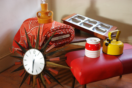 selection of vintage homewares recently acquired by H is for Home including a bolt of vintage orange Draylon fabric, Metamec starburst clock, bright yellow camping kettle, Old Hall teak & stainless steel serving dish, red & white polka dot Kirkham Pottery lidded pot, 1950s footstool with red vinyl seat, vintage yellow glazed pottery lamp base