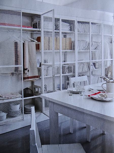 Tall, white wire cage storage in a modernist mill featured in Elle Decoration magazine