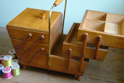 open vintage wooden sewing box with reels of thread