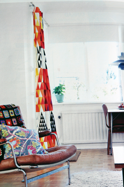 page from Swedish interiors magazine featuring vintage chrome & leather chair and colurful vintage fabric curtain