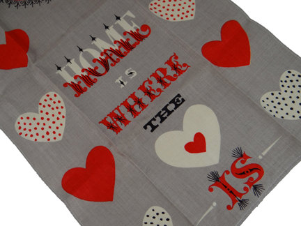 "detail from a Tammis Keefe teatowel with red & white hearts and the words, ""Home is where the heart is"""