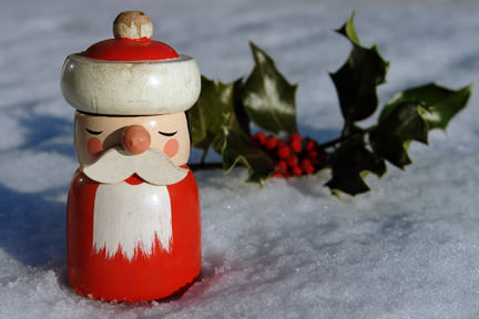 vintage wooden Father Christmas nutcracker standing in the snow with a sprig of holly
