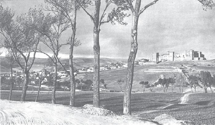 Sigüenza (Guadalajara), año 1930 o anterior. Se aprecia en primer plano una carretera con firme de tierra, flanqueada por árboles que dejan ver en segundo plano la carretera de Alcolea, igualmente arbolada, y la ausencia casi total de edificaciones entre el fotógrafo y el castillo, en aquel entonces todavía en buen estado