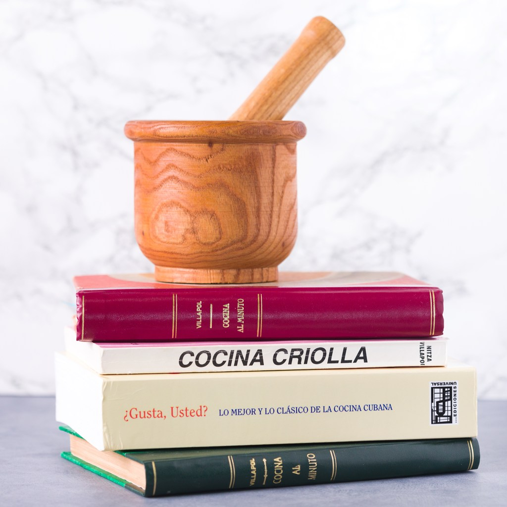 stack of cookbooks with a mortar and pestle on top. food and identity
