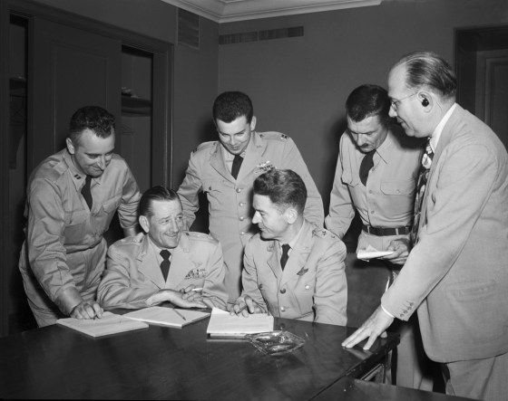 Captain Edward Ruppelt, standing, and General John Samford, seated to the right of him, discussing the reports of unidentified flying objects with other Air Force officers at a 1952 news conference.