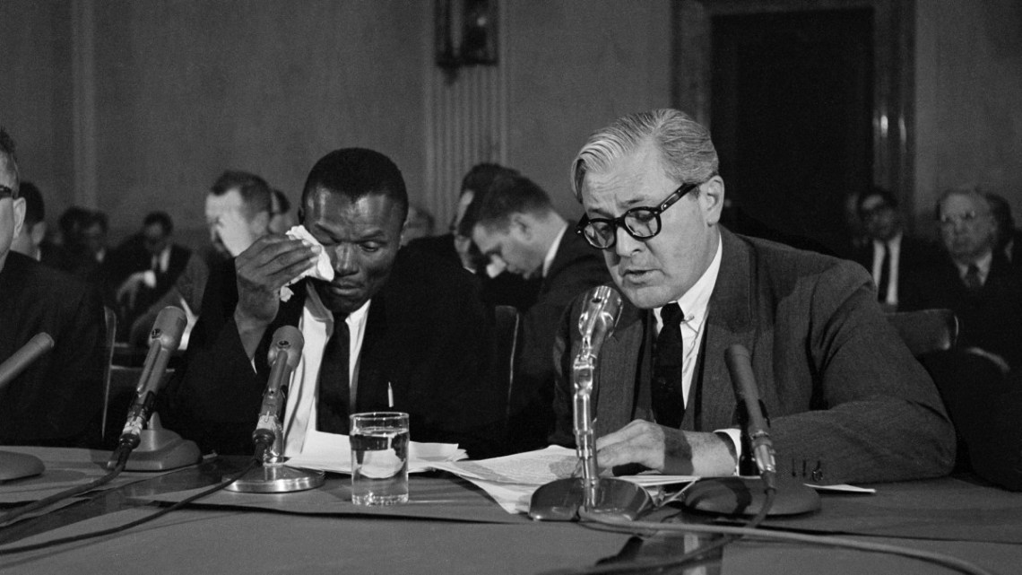 Melvin I. Belli, right, a San Francisco lawyer, reads a statement for his weeping client, Bernard S. Garrett, in an appearance before the Senate Investigations Subcommittee in Washington, April 1, 1965. Garrett broke down on the witness stand while trying to explain his role in a real estate mortgage deal blamed for the collapse of a Marlin, Texas bank.