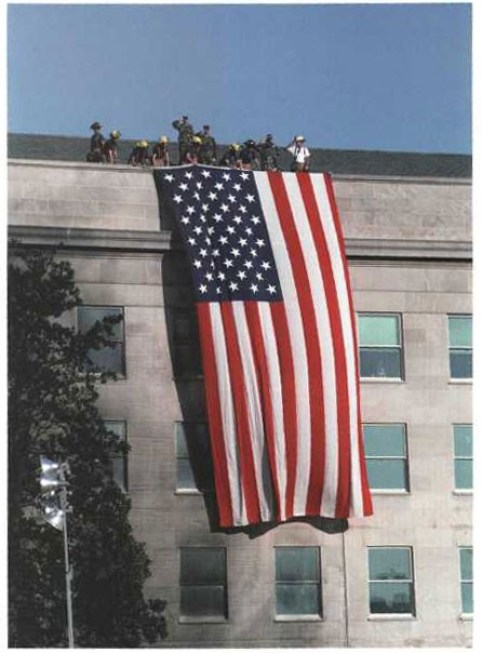 Firefighters and military personnel unfurl the flag from the Pentagon roof during President Bush's visit on 12 September 2001.