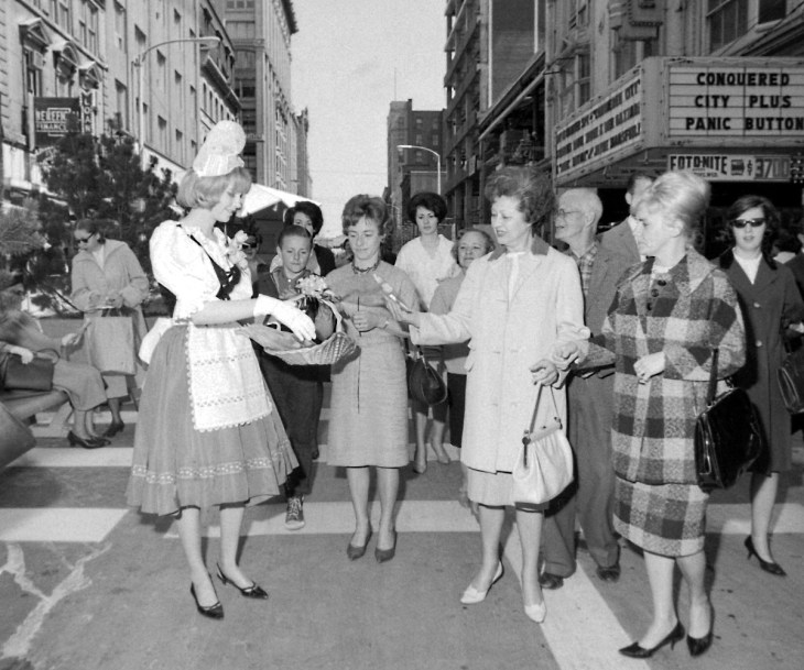RA Queen Marilyn Dorion hands out Riggio cigarettes during the 1965 Tulip Festival parade. The Toronto-Dominion Branch is visible behind, under construction. Image: Ted Grant / LAC Series 65-0149.