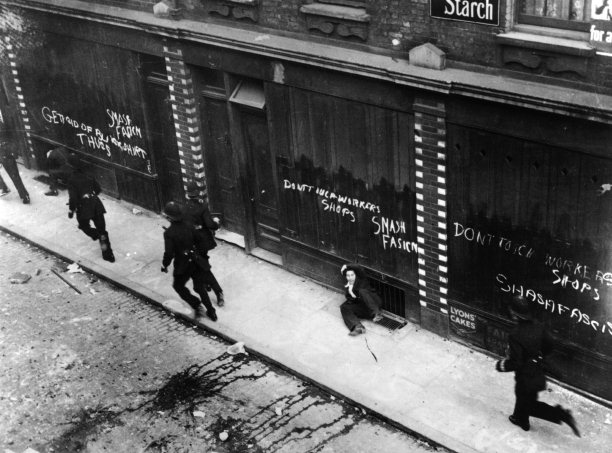Demonstrators are chased by police past East End shops daubed with antifascist and Communist slogans, October 4th, 1936. Photo / Getty