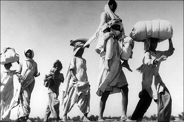 Old Sikh man carrying his wife on their move to their new home, 1947.