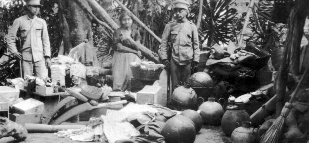 """Hand-written caption on the back of the photo: """"Communist woman with all the stolen goods."""" Items include clay jugs and corn grinders."""