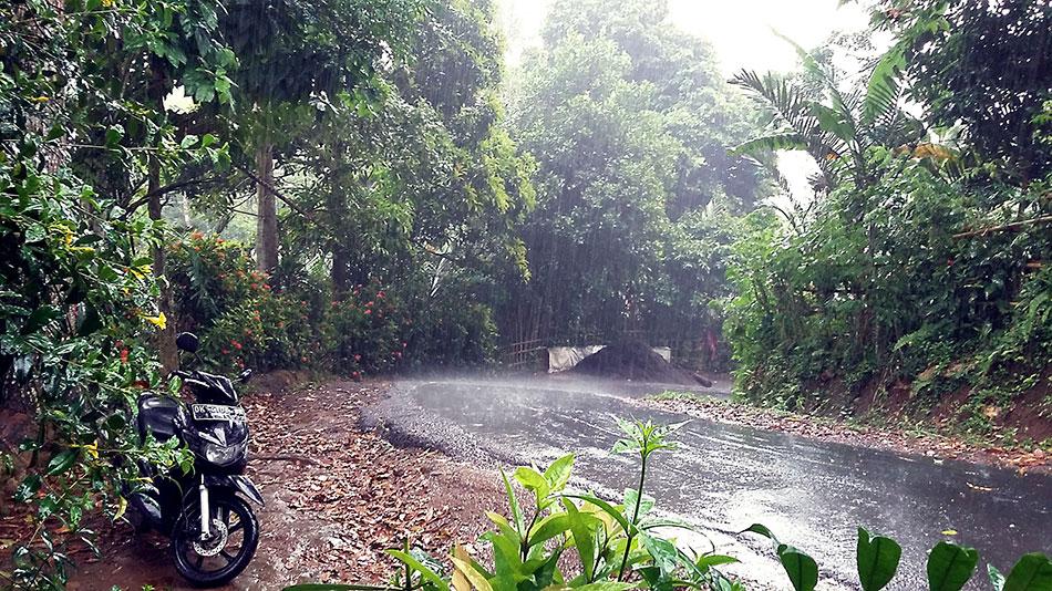 Conduite d'un scooter à Bali sous la pluie.