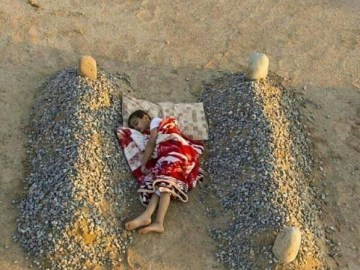 Photograph Showing a Child in Syria, Sleeping Between his Parents' Graves