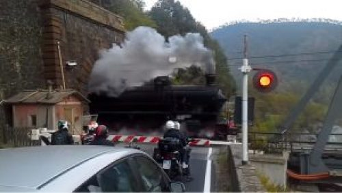 Image of Heritage train towed by Italian steam locomotive FS Class 740 at a level crossing in Ovada, Italy