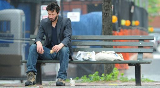 Photograph of Keanu Reeves sitting on a Bench