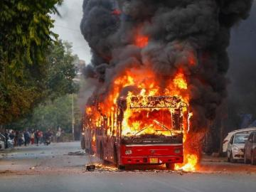 Image about Delhi Police Pour Fuel to Burn a Bus During CAA Protests