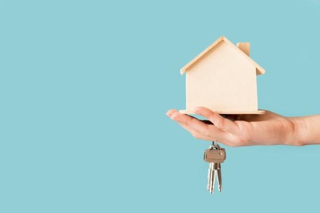Hand holding keys and miniature house.