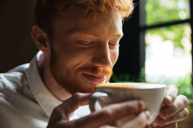Man sniffs coffee with closed eyes.