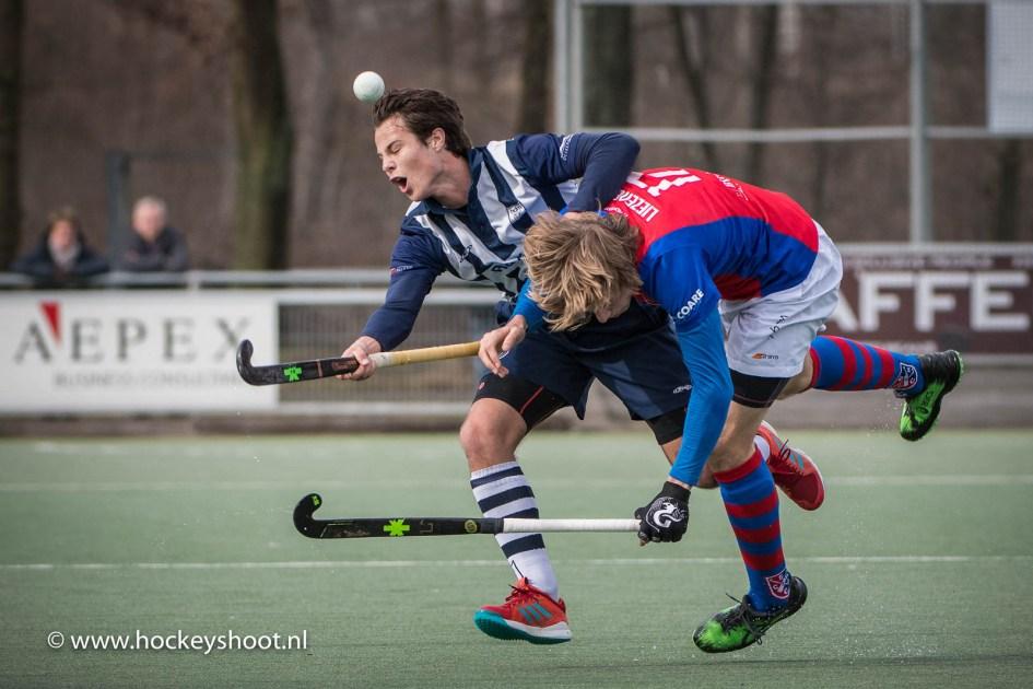 Rick van den IJssel (hdm) in de clinch met Friso Liezenberg (SCHC)