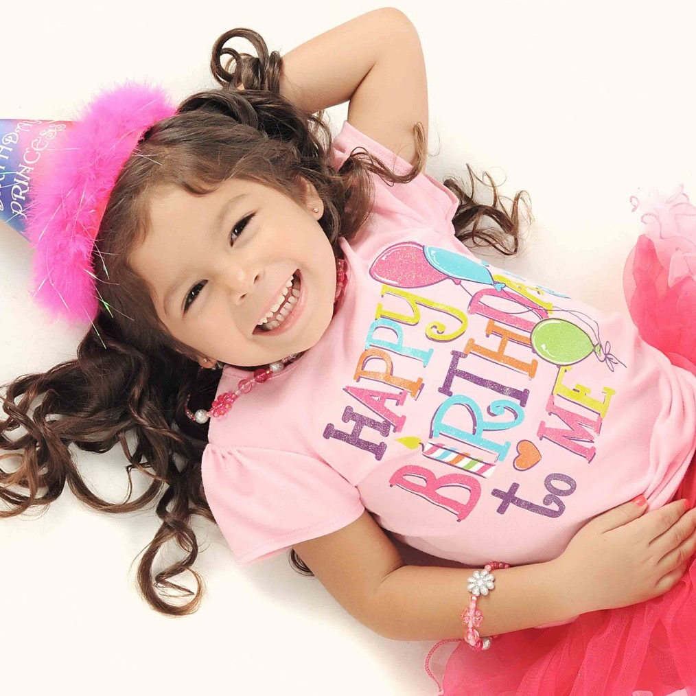 Young girl wearing a party hat and t-shirt