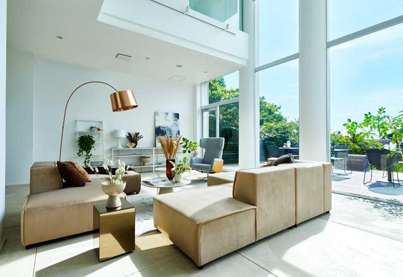 Salón moderno con grandes ventanales con salida directa al jardín, sofás beis y lámpara de cobre