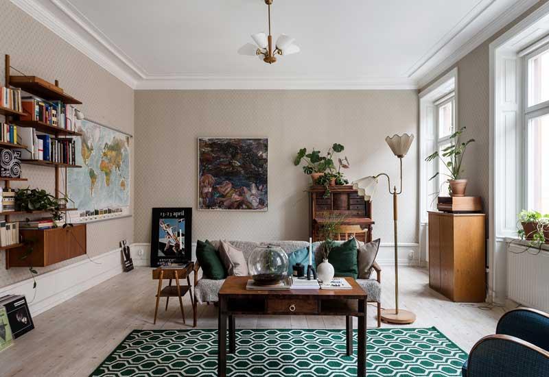 Salón decorado con muebles 'vintage' de madera oscura y alfombra en tonos verdes