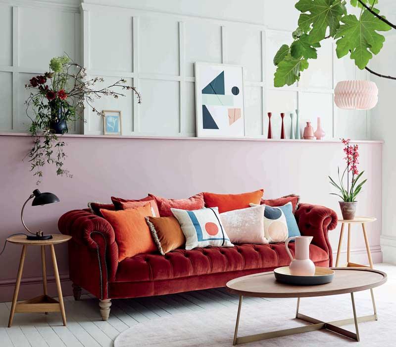 Estar con pared pintada en dos colores (verde y rosa) y sofá en burdeos