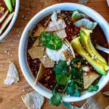 Rich and savory, this simple Instant Pot Chicken Tortilla Soup gets its flavor from a rich chile broth made from charred onions, garlic, tomatoes, and dried guajillo and ancho chiles. The best part? The entire thing from the homemade tortilla chips to the soup can be made in the Instant Pot! #instantpot #chickentortillasoup #tortillasoup #instantpotrecipe