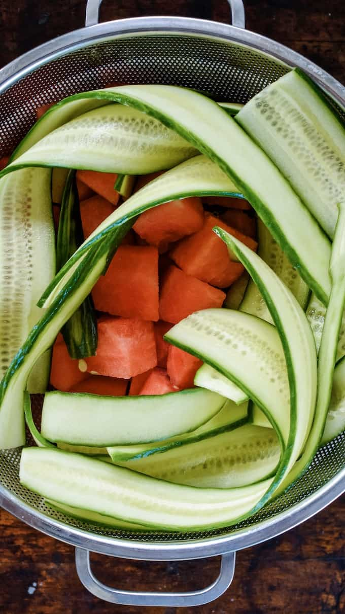 Cucumber strips and watermelon chunks in a colander, waiting to be made into Cucumber-Watermelon Salad. #holajalapeno