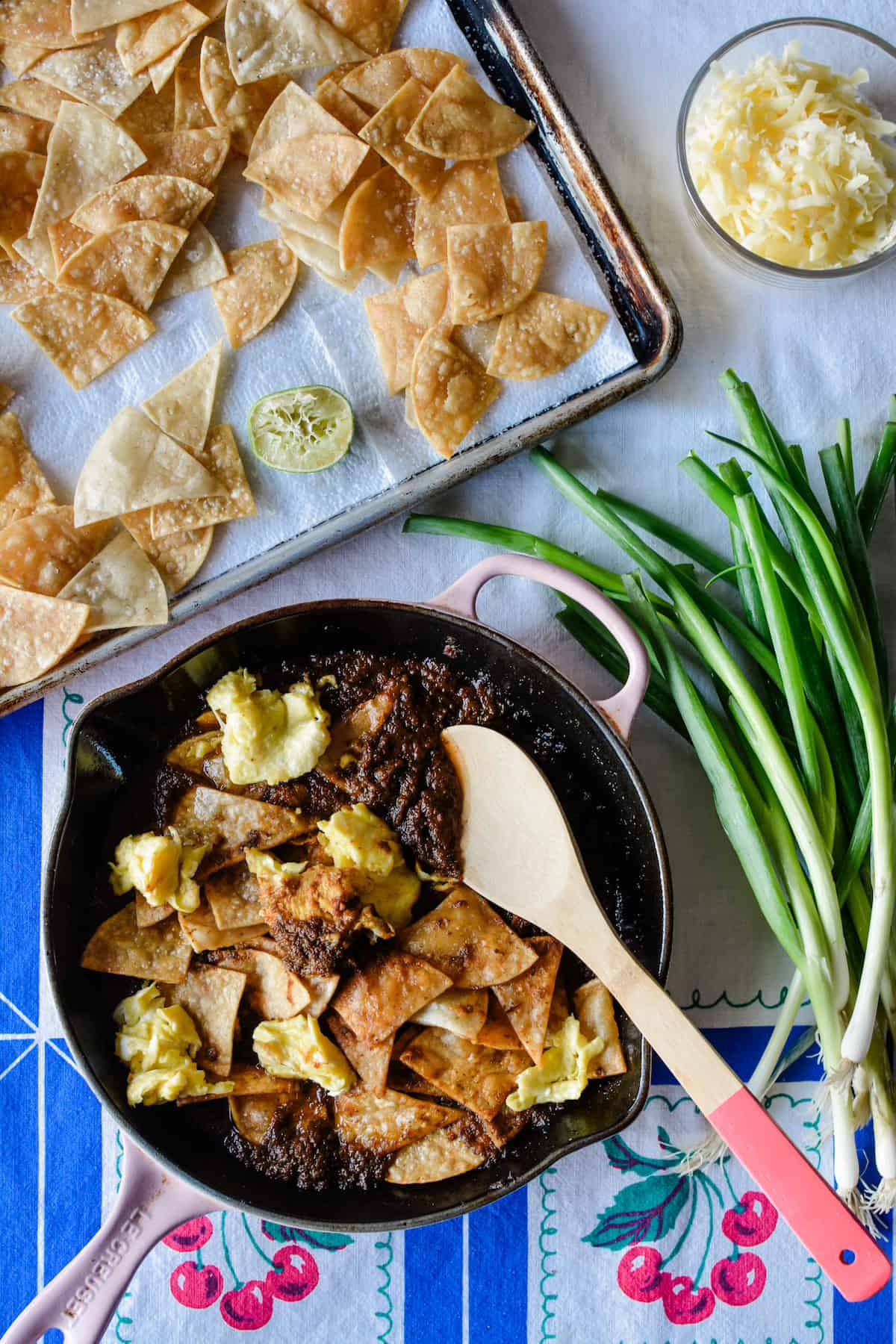 An overhead image of Mexican chilaquiles in a frying pan with scallions to one side and a bowl of grated cheese on another.
