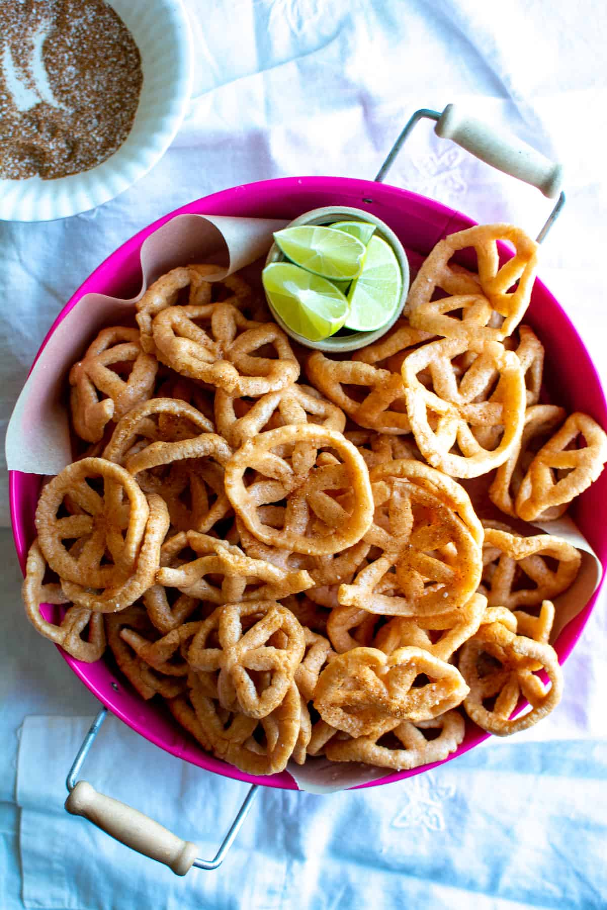 Overhead image of Mexican pinwheel chips in a pink tray with a dish of lime wedges on the side and a bowl of spice mix.