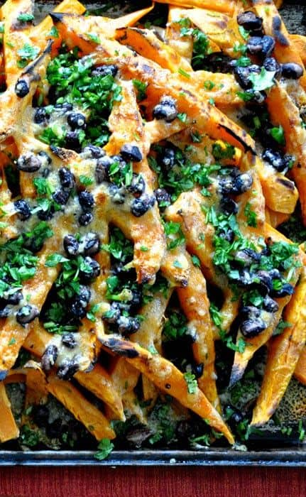 Close up of a pan of sweet potato nachos with black beans and chopped cilantro.