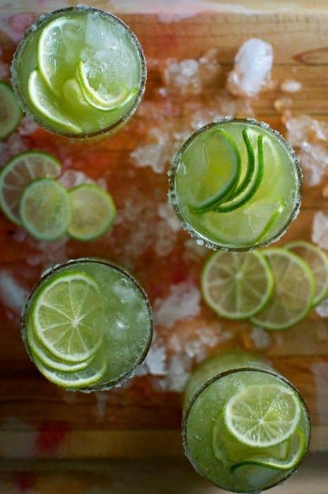 Four glasses on a wooden cutting board filled with ice, cucumber margarita, and lime wheels.