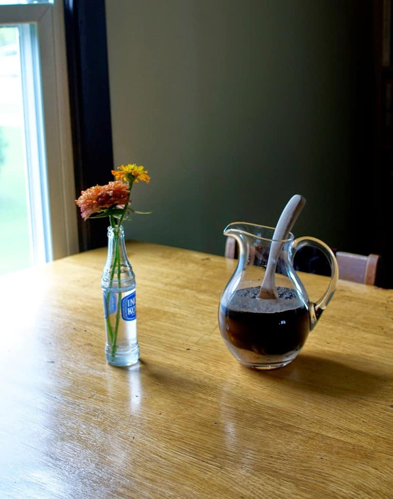 Coffee grounds, rice, coconut, and sugar soaking in water in a glass pitcher on a wood table next to a jar of flowers.