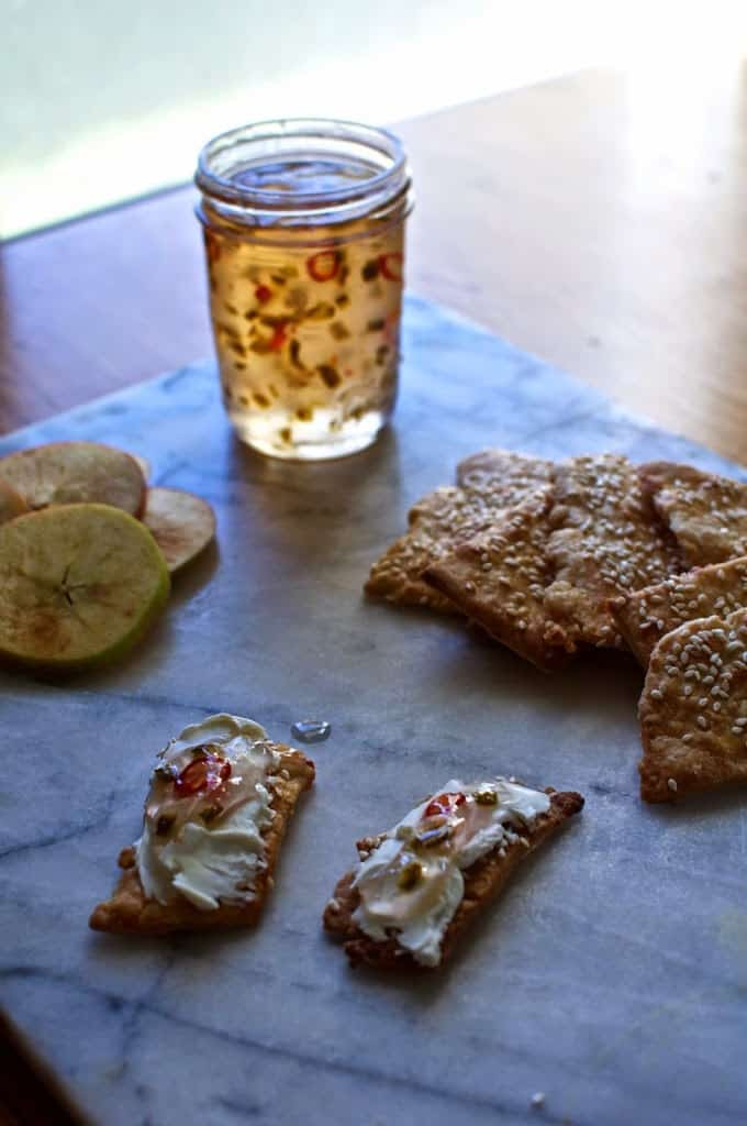 A open jar of jalapeno jelly sitting on a marble slab with apples and crackers near by.