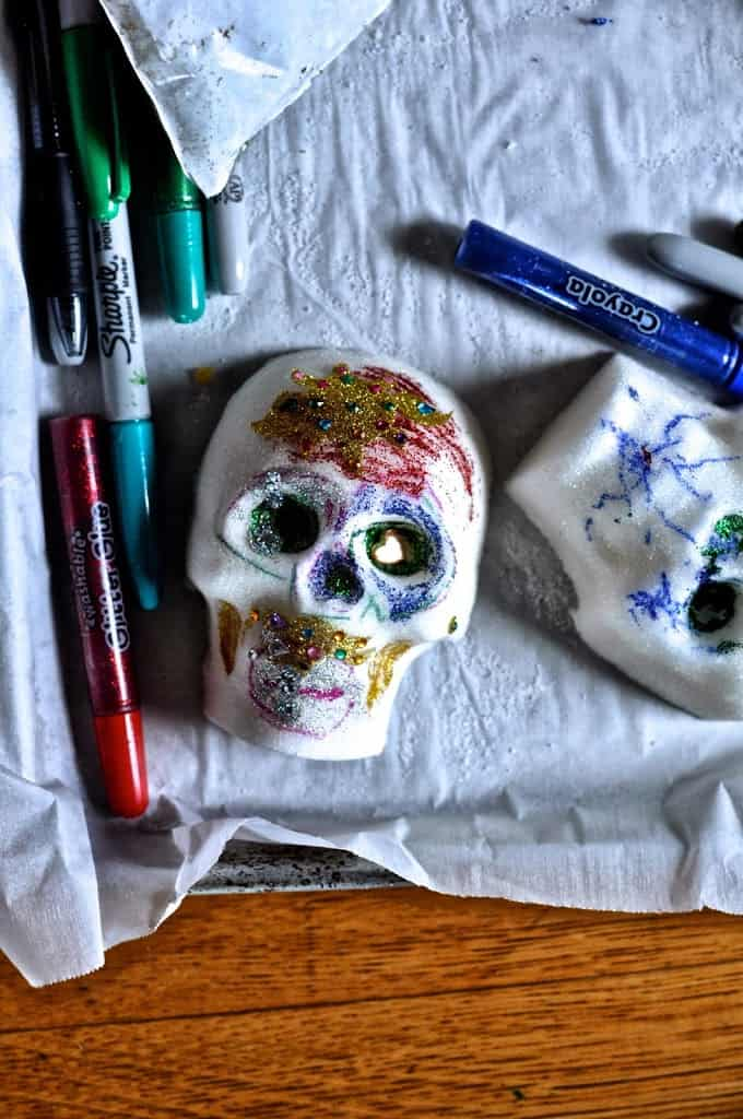 Decorated sugar skulls sitting on a parchment-lined baking sheet next to markers and glitter glue.