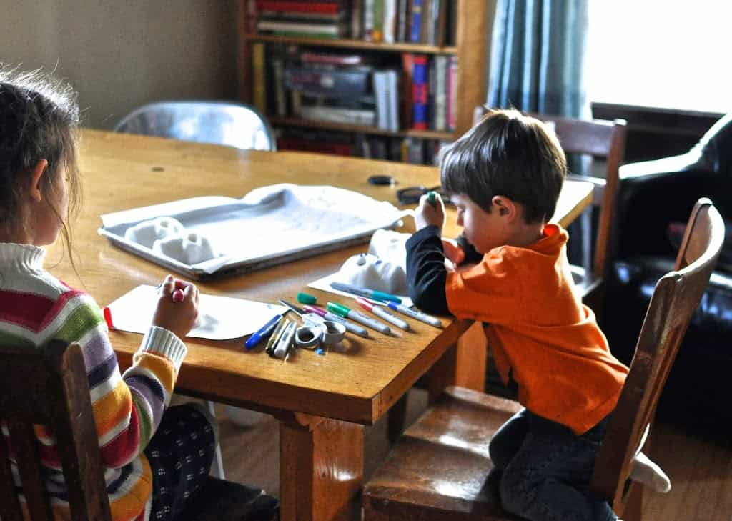 Two small children sitting at a wood table with markers and craft supplies decorating sugar skulls.