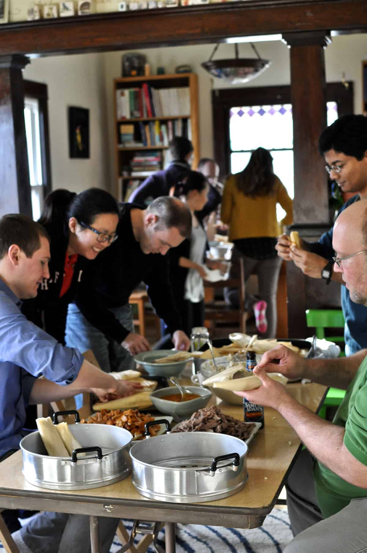 Several people gathered around a folding table making tamales.