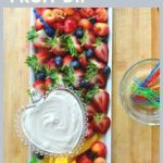 A platter of fruit with a bowl of sour cream dip on top.