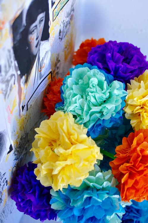 Colorful tissue paper flowers in yellow, light blue, orange, and purple.