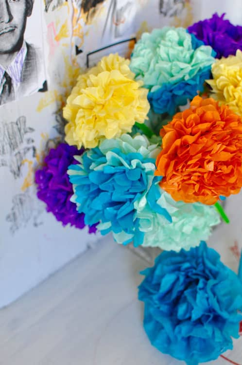 A bouquet of tissue paper flowers sitting on an altar for Day of the Dead.