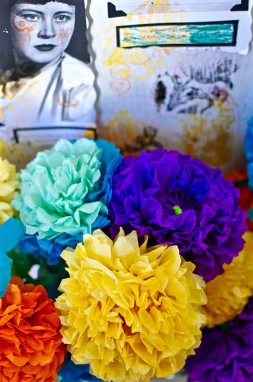 Colorful tissue paper flowers sitting on an altar for Day of the Dead.