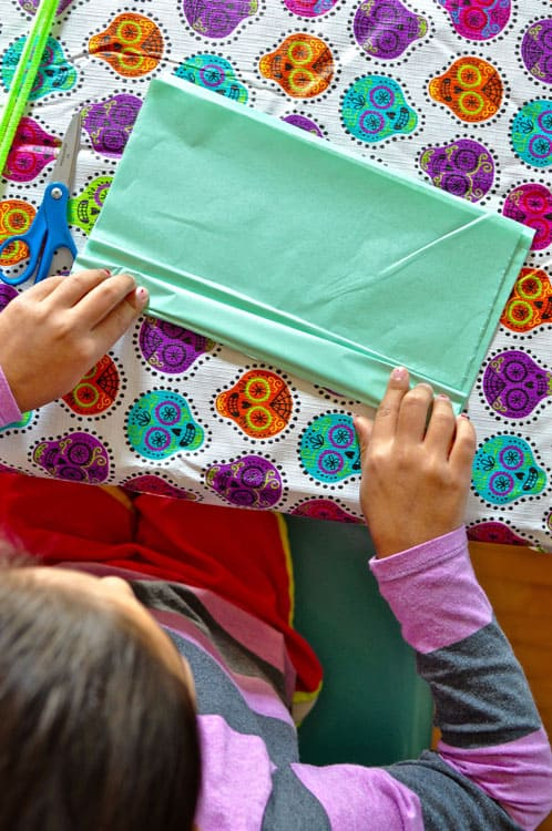 Girl folding light blue tissue paper on top of a Calavera tablecloth with a pair of scissors.