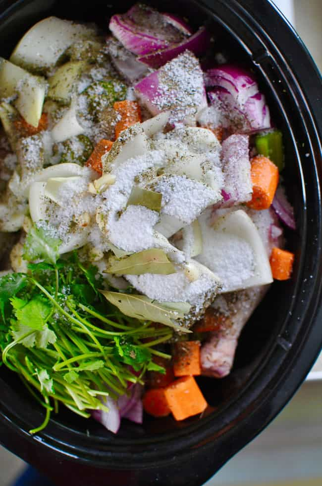 An overhead image of all the ingredients to make Caldo de Pollo in the black insert for a Crock Pot including chicken, cilantro, and carrots.